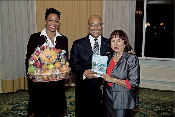 Angela Cleare presenting the Minister of Tourism with the book and a fruit basket for his support and contributions.