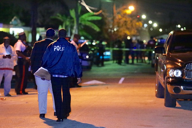 POLICE officers at the scene of Sunday night's fatal shooting in Yellow Elder Gardens. Photo: Terrel W Carey/Tribune Staff
