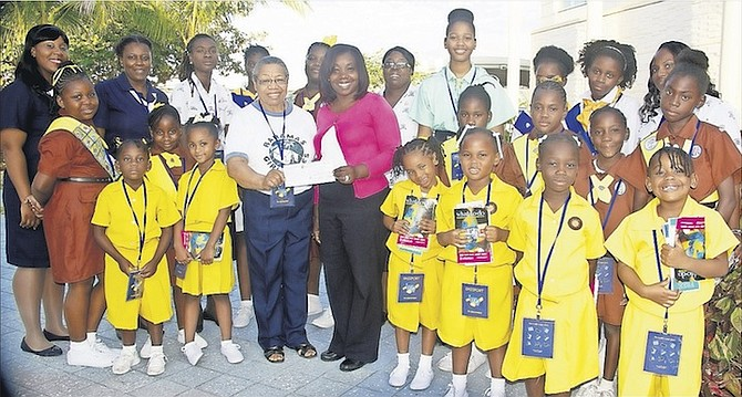 Sunflowers, brownies, guides, rangers and their leaders toured LPIA to explore careers in the fields of science and technology. Pictured in the centre is Anita Bernard, president of the Bahamas Girl Guide Association accepting a cheque from Elizabeth Ferguson, duty supervisor and tour guide at NAD.