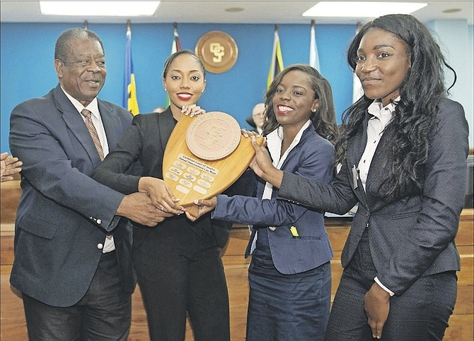 Caribbean Court of Justice President Sir Dennis Byron presents the International Law Moot Court Competition trophy to Raven Rolle, Megan Curry and Janessa Murray, of the Eugene Dupuch Law School, in Trinidad and Tobago.