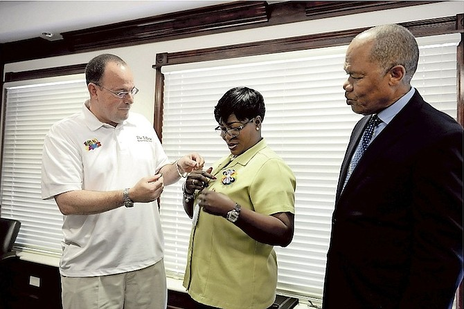 Veronica Ferguson receives her recognition pin from Kevin Darville, the Tribune Media Group's special projects co-ordinator, as the February winner of the PHA Unsung Heroes award, watched by Herbert Brown, managing director of the Public Hospitals Authority.  Photo: Shawn Hanna/Tribune Staff