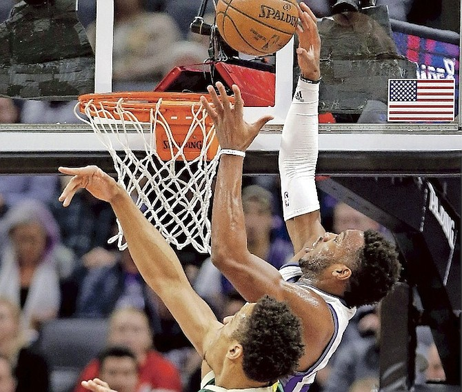 Kings guard Buddy Hield, right, goes to the basket against Bucks guard Malcolm Brogdon during the first half of Wednesday night's game in Sacramento, California.