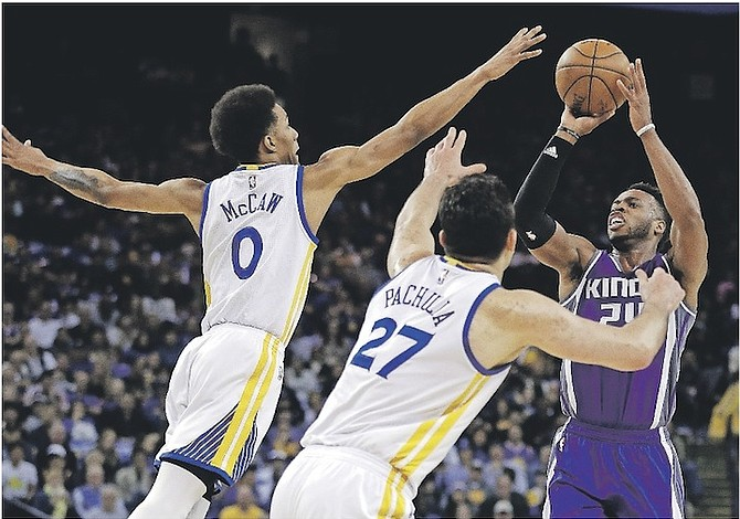 Sacramento Kings' Buddy Hield, right, shoots against Golden State Warriors' Patrick McCaw, left, and Zaza Pachulia (27) during the first half of Friday's game. 