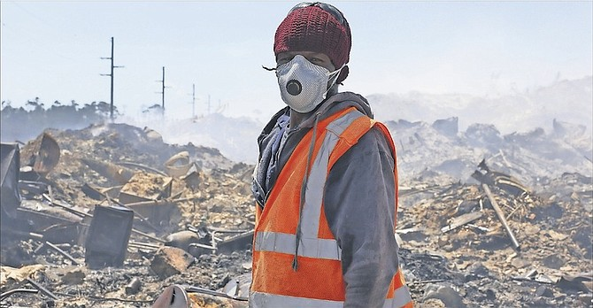 A worker in a protective mask at a dump fire earlier this year. Photo: Terrel W. Carey/Tribune Staff