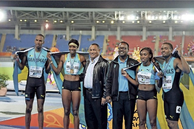 JOB WELL DONE: Prime Minister Perry Christie (3rd from left) and Minister of Youth, Sports and Culture Dr Daniel Johnson (3rd from right) share a special moment with the gold-medal winning mixed relay team of Steven Gardiner (far left), Shaunae Miller-Uibo, Anthonique Strachan and Michael Mathieu (far right). Photo: Shawn Hanna/Tribune staff