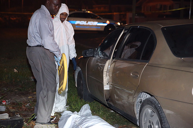 Investigators at the scene of the fatal shooting of a man in a car at Whitaker Close early on Friday. Photo: Terrel W Carey/Tribune Staff