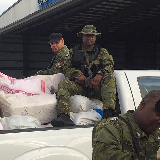 Officers in South Andros with some of the seized nylon sacks of marijuana on Thursday