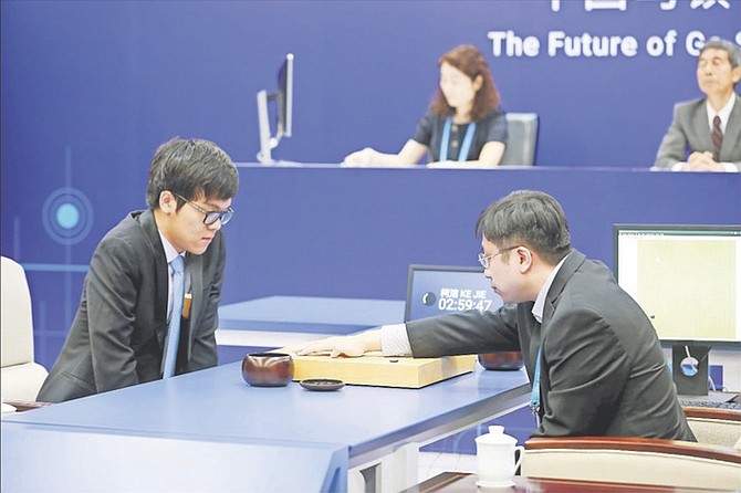 Chinese Go player Ke Jie, left, looks at the board as a person makes a move on behalf of Google's artificial intelligence program, AlphaGo, during a game of Go at the Future of Go Summit in Wuzhen in eastern China's Zhejiang Province. (Chinatopix via AP)
