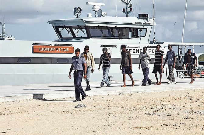 A marine escorts Haitian migrants off the patrol craft HMBS Lignum Vitae at the Coral Harbour Base shortly after they were apprehended early Monday morning. They were discovered in the central Bahamas on July 3. Photo: RBDF Public Relations Department