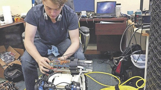 Ian Switzer, an engineer at American Marine Research Company, works on a drone in Pensacola, Fla. The company is designing robots to autonomously detect and collect lionfish.  (Joseph Baucum/Pensacola News Journal via AP)