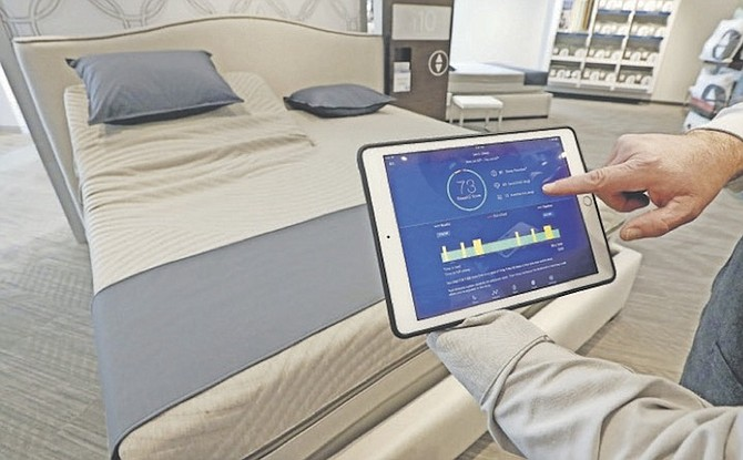Sleep Number store manager Lee Pulliam demonstrates how the company's sleep technology tracks your sleeping patterns. (AP)