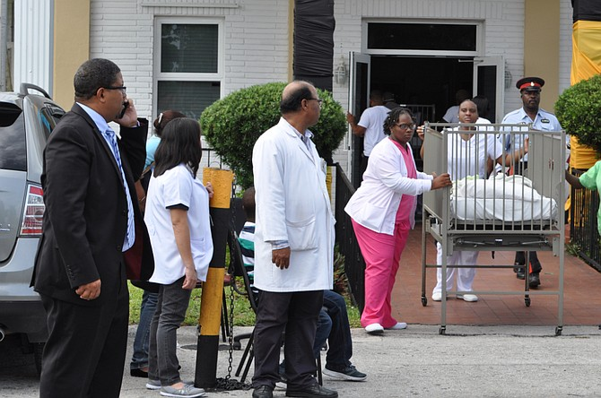Patients are evacuated from the hospital as Deputy Prime Minister K Peter Turnquest looks on.