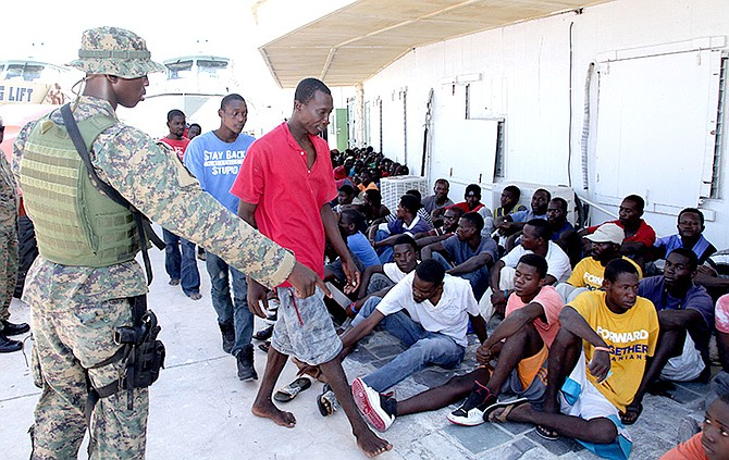 A Royal Bahamas Defence Force marine is pictured giving directions to some of the Haitian migrants at the RBDF Base on July 26. Photo: RBDF Marine Seaman Kyle Smith