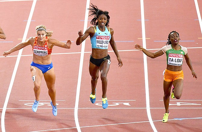 Netherlands' Dafne Schippers, left, crosses the finish line to win the Women's 200 metre final from Ivory Coast's Marie-Josee Ta Lou, right, and Shaunae Miller-Uibo, centre, at the World Athletics Championships in London Friday, Aug. 11, 2017. (AP Photo/Martin Meissner)