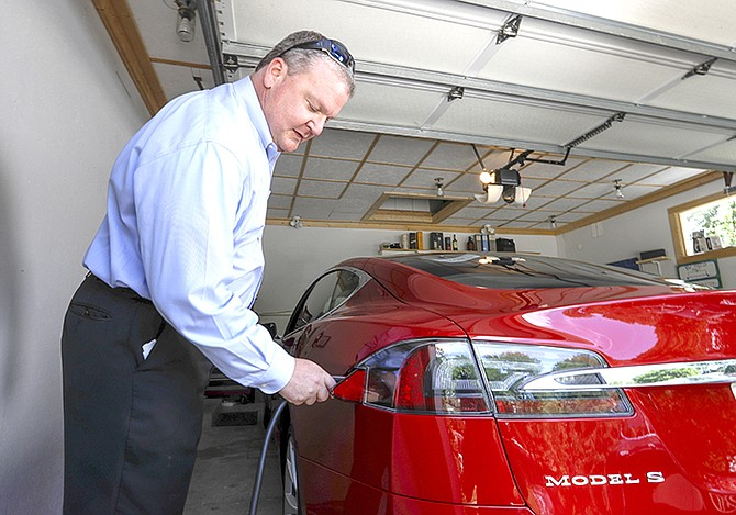 Jeff Solie plugs in his electric Tesla sedan at his home, in New Berlin, Wis. Electric cars are seeing growing support around the world. But there's a problem: There aren't enough places to plug those cars in. The nearest fast-charging Tesla Superchargers are 45 miles (72 kilometres) away. There are some public charging stations in nearby Milwaukee, at hotels and shopping centres, but Solie relies almost entirely on the charging system he set up in his garage.  (AP Photo/Morry Gash)