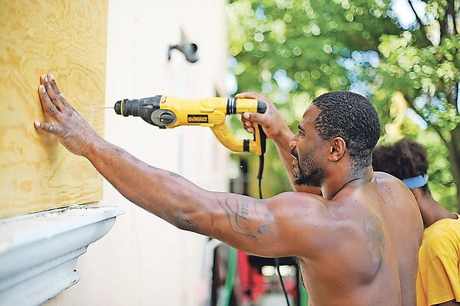 Bahamians making preparations to ensure the safety of their homes yesterday. Photo: Terrel W. Carey/Tribune Staff