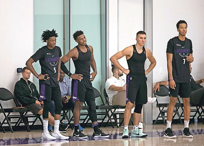 Sacramento Kings' (from left) De'Aaron Fox, Buddy Hield, Bogdan Bogdanovic and Skal Labissiere stand on the sideline yesterday during a drill at the NBA team's training camp in Sacramento, California. (AP)
