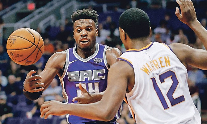 Sacramento Kings guard Buddy Hield (24) loses the ball as Phoenix Suns forward TJ Warren (12) defends during the first half of an NBA basketball game, Monday, in Phoenix. (AP Photo/Matt York)