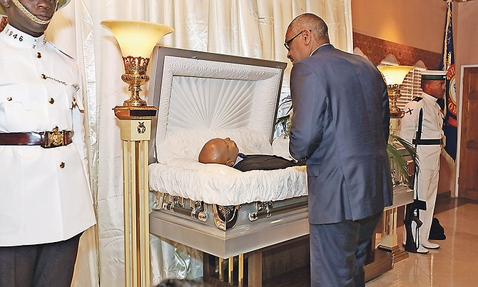 Prime Minister Dr Hubert Minnis views the body of the late Calvin Johnson, former MP for the Free National Movement. Photo: Terrel W. Carey/Tribune Staff
