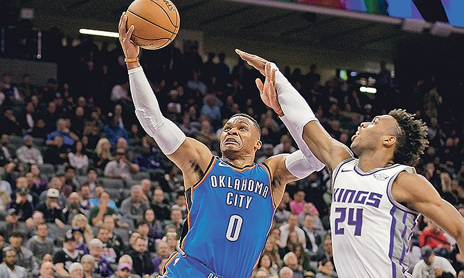 Thunder guard Russell Westbrook, left, goes to the basket against Kings guard Buddy Hield on Tuesday night in Sacramento, California.