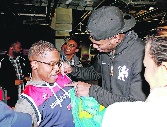 Bahamian NBA star Buddy Hield autographs the jersey of a Wizards fan.