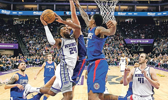 Sacramento Kings guard Buddy Hield, left, goes to the basket against Los Angeles Clippers' Blake Griffin, rear, and Lou Williams, front right, in the second half of Saturday's game in Sacramento, California. The Clippers won 97-95.