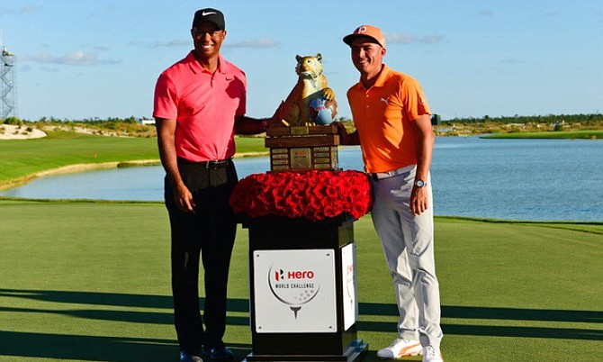 Rickie Fowler, right, poses with Tiger Woods and the trophy after Fowler won the Hero World Challenge golf tournament at Albany Golf Club in Nassau, Bahamas, Sunday. (AP Photo/Dante Carrer)