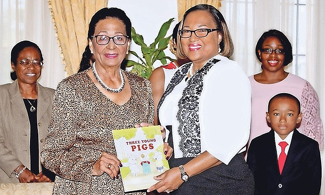 Author Lisa McCartney presents her book to Governor General Dame Marguerite Pindling.