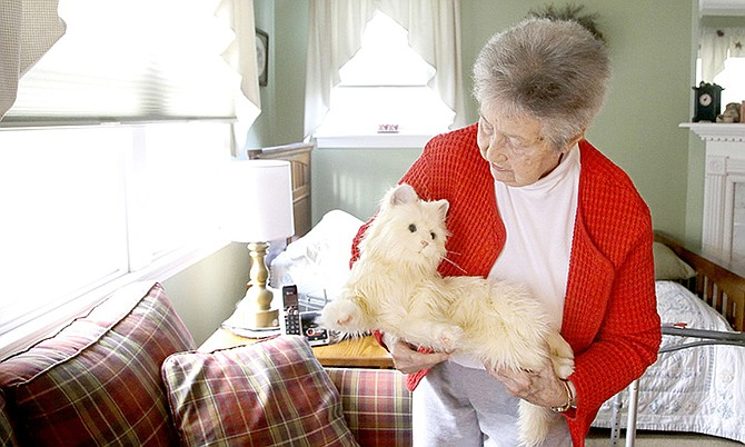 "93-year-old Mary Derr holds her robot cat she calls ""Buddy"" as she talks to it in her home she shares with her daughter Jeanne Elliott in South Kingstown, R.I. Derr has mild dementia, and Elliott purchased a ""Joy for All"" robotic cat earlier this year to keep her mother company. (AP Photo/Stephan Savoia)"