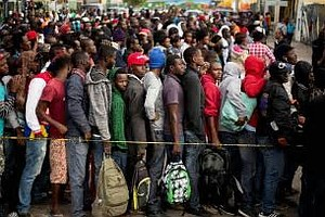 Lining up in Mexico to cross over into USA, but Mexicans warning them that they will be arrested there.