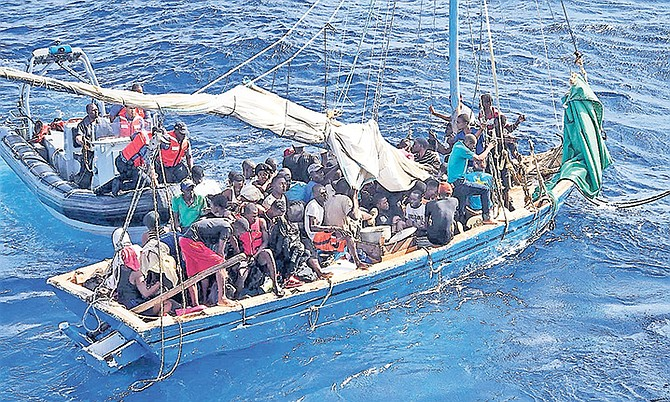 THE RBDF boarding team apprehending 87 Haitian migrants off Great Inagua on Saturday, December 23. Photo: USCG