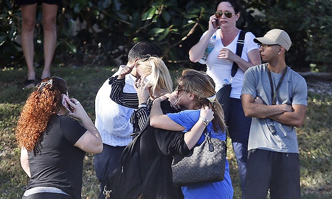 Anxious family members wait for news of students as two people embrace, Wednesday, in Parkland, Florida. (AP Photo/Wilfredo Lee)