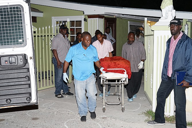 Police remove the body of one of the victims from Saffron Street, Pinewood Gardens, on Friday night.