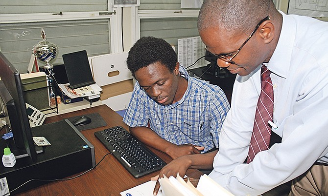 Manager of BTVI's Technical Services Wellington Bain is pictured in discussion with Office Administration student Tyric McPhee, who is a work study student in his department. Photo: Shantique Longley