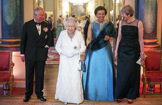 Britain's Queen Elizabeth II, second left, Prince Charles, Commonwealth Secretary-General Patricia Scotland and Prime Minister Theresa May walk in the Blue Drawing Room at Buckingham Palace as the Queen hosts a dinner during the Commonwealth Heads of Government Meeting, in London, Thursday. (Victoria Jones/Pool Photo via AP)