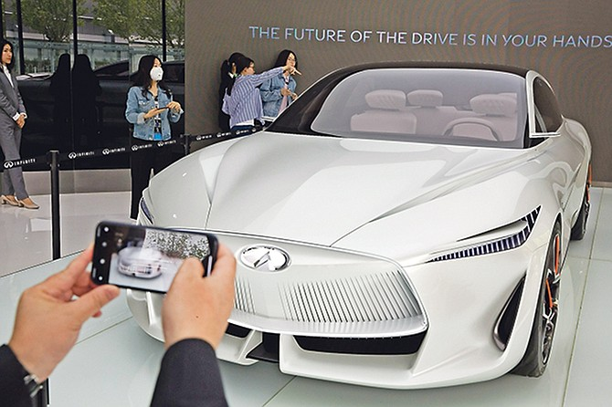 Visitors look at the Infiniti electric concept sedan at a showroom ahead of the Auto China 2018 to be held in Beijing, China. Photo: Ng Han Guan/AP