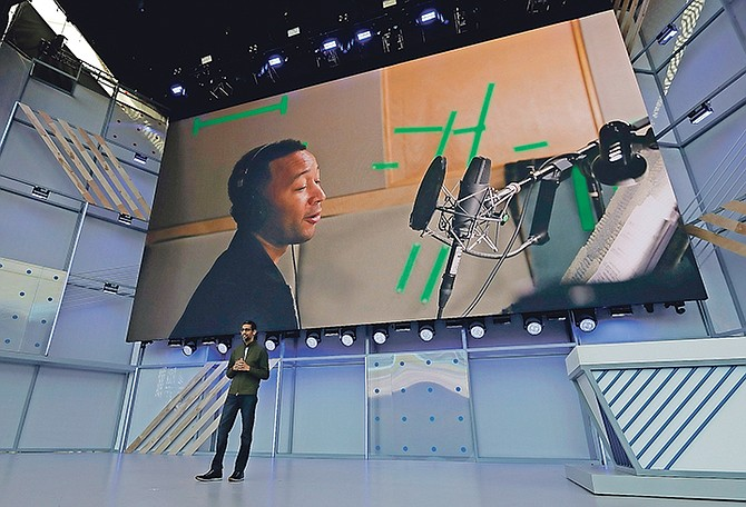 Google CEO Sundar Pichai speaks under a video showing singer John Legend at the Google I/O conference. 