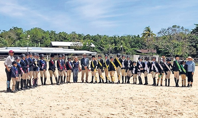 PROUD riders receive their ribbons - (l-r): Mrs Erika Adderley-Coello, coach; Lyford Cay School Team riders; Queens College Team riders; Mrs Elizabeth Williams, Vice-President of Equestrian Bahamas;