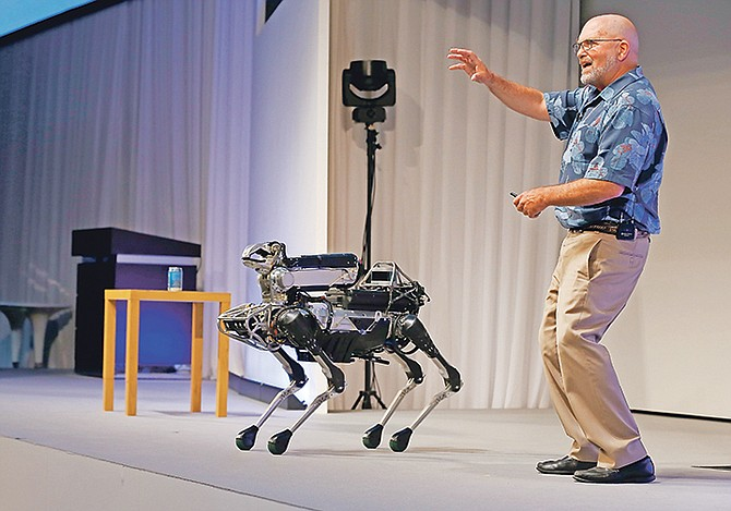 Boston Dynamics chief executive Marc Raibert speaks about his four-legged robot SpotMini during a SoftBank World presentation at a hotel in Tokyo. The robotics company known for its widely shared YouTube videos of nimble, legged robots opening doors or walking through rough terrain is finally preparing to sell some of them after years of research. Raibert said his company will begin selling the dog-like SpotMini robot next year, likely to businesses for use as a camera-equipped security guard. He made the announcement at a TechCrunch robotics conference at University of California, Berkeley. Photo: Shizuo Kambayashi/AP