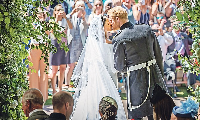 Prince Harry and Meghan Markle kiss on the steps of St George's Chapel at Windsor Castle following their wedding on Saturday. Photo: Danny Lawson/AP