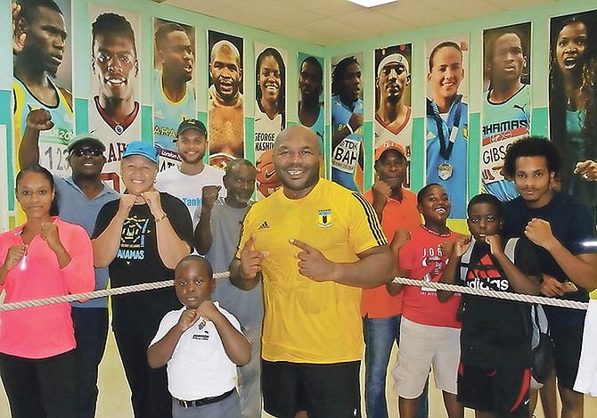 BAHAMIAN pro boxer Sherman 'The Tank' Williams (centre) at his first public training workout session at the YMCA with executive director Karen Johnson and some of the youngsters.