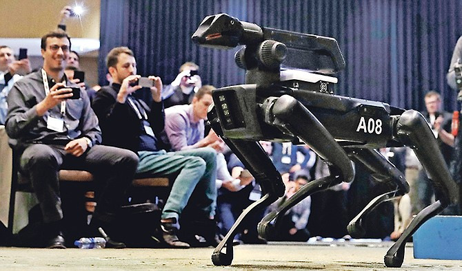 A Boston Dynamics SpotMini robot walks through a conference room during a robotics summit in Boston. It's never been clear whether robotics company Boston Dynamics is making killing machines, household helpers, or something else entirely. But the secretive firm, which for nine years has unnerved viewers with YouTube videos of robots that jump, gallop or prowl like animal predators, is starting to emerge from a quarter-century of stealth. Photo: Charles Krupa/AP