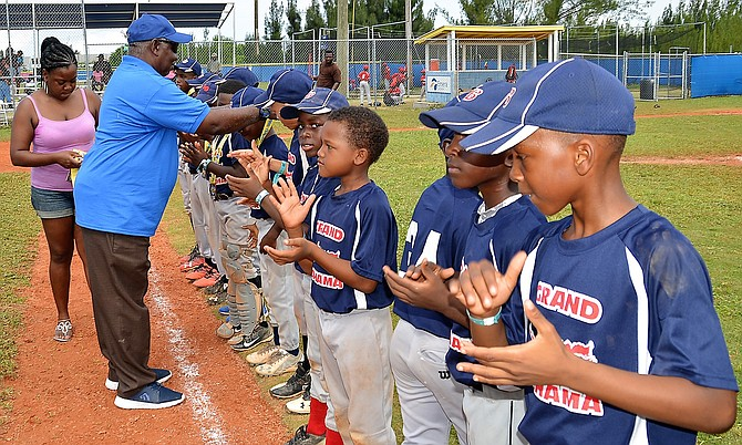 BBA president Sam Rodgers presents medals to Grand Bahama Little League players. Photo: Dereck Carroll