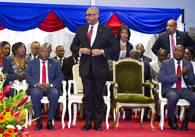 In this March 2017 file photo, Haiti's Prime Minister Dr. Jack Guy Lafontant stands on stage during his confirmation ceremony at the National Palace, in Port-au-Prince, Haiti. Lafontant resigned Saturday, amid criticism for his failed attempt to increase fuel prices. (AP Photo/Dieu Nalio Chery, File)