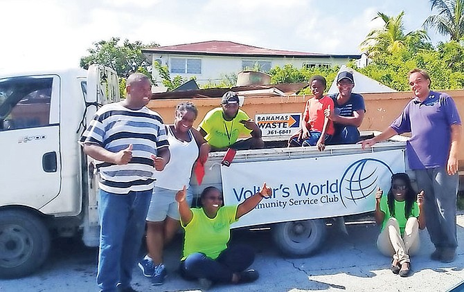 The executive members of Voltar's World on-site at Millar Heights posing in front of a Bahamas Waste bin.
