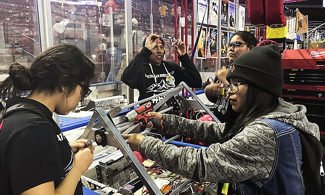 From left, Navajo Mountain High School students Nahida Smith, Myra King and Breana Bitsinne competing in a Utah regional robotics competition in West Valley City, Utah in March. The team, from a remote town in southern Utah, is now headed to an international robotics competition next week in Mexico City, Mexico. They were invited to compete in the First Global Challenge, which will draw teams from 190 countries to create robots capable of feeding power plants and building environmentally efficient transmission networks. Photo: Heather Anderson/AP