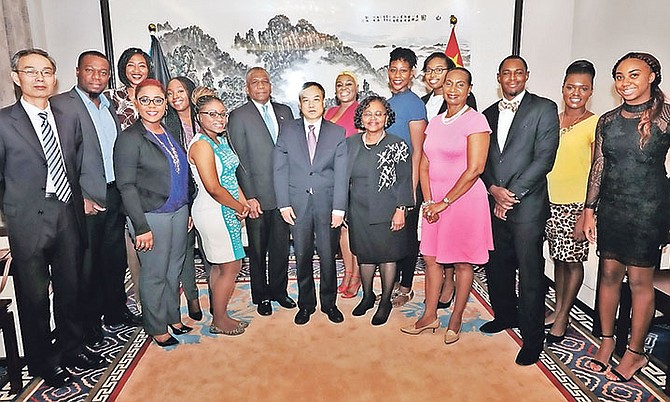 Chinese Ambassador Huang Qinguo, centre, with Permanent Secretary at the Ministry of Foreign Affairs Jack Thompson, other officials and Bahamian recipients of Chinese scholarships at a recent reception at the Chinese Embassy. Photo: Eric Rose/BIS
