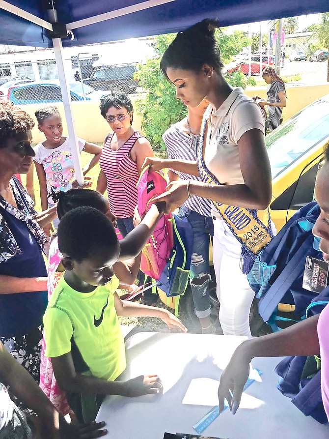 Miss Bahamas Grand Dannise Bain hands out backpacks at her first back-to-school event.