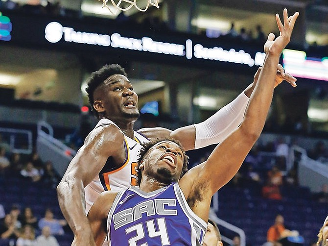 Sacramento Kings guard Buddy Hield (24) has his shot blocked by Phoenix Suns centre Deandre Ayton, left, during the first half of Monday night's preseason game in Phoenix. (AP)