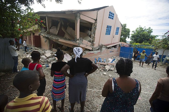 Residents stand looking at a collapsed school damaged by a magnitude 5.9 earthquake the night before, in Gros Morne, Haiti, Sunday. (AP)